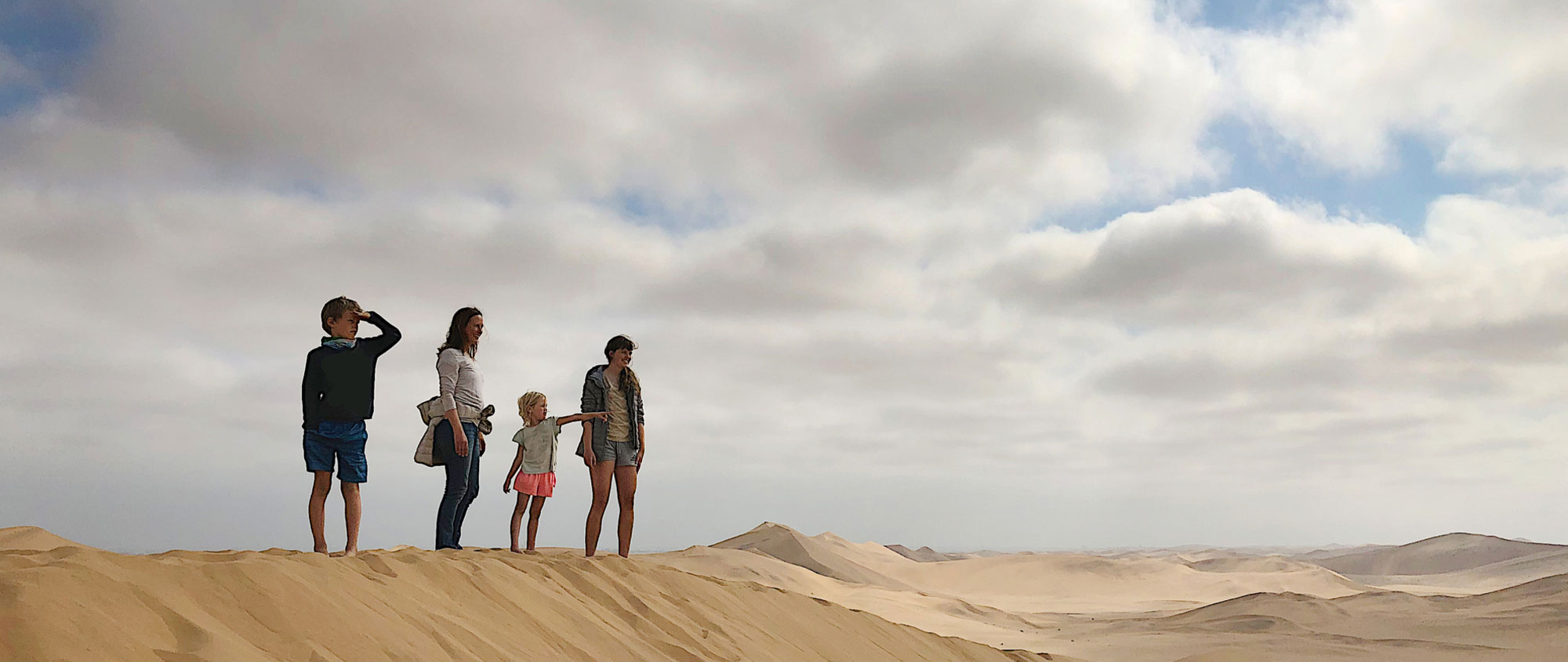 Family standing on dunes, Namibia